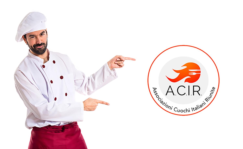 Foto di un cuoco con divisa bianca e parannanza rossa, che indica il logo dell'associazione ACIR (Associazioni Cuochi Italiani Riunite).