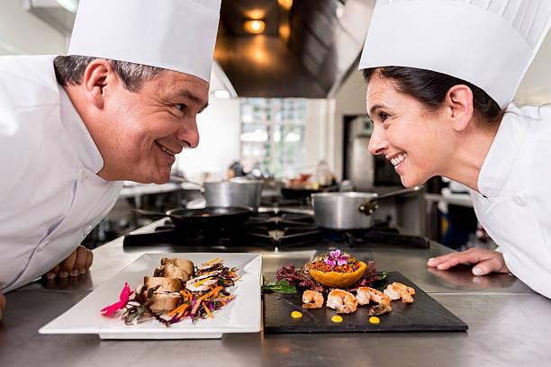 immagine di due cuochi che si fronteggiano l'uno davanti all'altra, davanti a un tavolo con sopra due piatti di cibo accuratamente preparati.